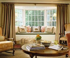 Filling the Bay: Sometimes the best option is to keep the fabric in the room when a window seat fills the bay window. These draperies draw closed over the bay, bracketing the space in soft color.
