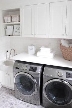 @JSHOMEDESIGN- Laundry room decor with beautiful white quartz counter tops, white beveled subway tiles, farmhouse sink, kohler faucet, patterned tiles.