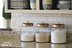 Glossy white subway tile with gray grout. Love the canisters - the tops were spray painted gold!