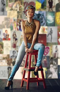 Full length portrait of an attractive young woman sitting on a stool