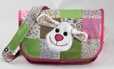 The set includes patchwork diaper bag equipped with six inner pockets and a sheep on the bag, three diapers with hearts, a bib with a heart, a wipes case with five wipes and a changing pad.