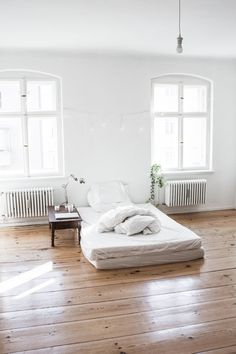 clean open space. love the wood floor, bright windows, comfy looking floor bed. // home + garden