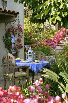 eChoose a color scheme. Sticking to two or three colors throughout the space will help your patio look polished and put-together. Here blue and yellow are used in the table setting and wall fountain, creating an exciting contrast with the vibrant pink bougainvillea.