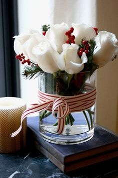 glass vase is classics, and white roses with red berries and evergreens it looks as a modern take on traditional