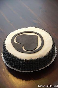 Täytekakku Ässät-faneille. Täytteenä suklaavaahtoa ja banaania. Päällä on valkoista ja mustaa sokerimassaa, reunat on pursotettu mustalla pastavärillä värjätyllä kermavaahdolla käyttäen pientä tähtityllaa.