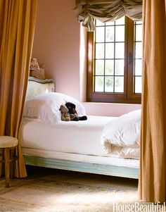 In designer Dana Abbott's comfortable and casual California home, a pale green antique French bed snuggles behind curtains in her youngest daughter's bedroom.   - HouseBeautiful.com