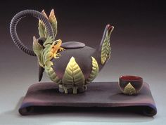 """""""Woodland Frog Tea"""" ceramic tea set created by Nancy Y. Adams.  Wheel thrown and hand-built earthenware teapot, tray and cup. Teapot and cup have a hand-carved leaf motif; teapot also has a hand-modeled frog motif. All items are decorated with airbrushed glazes. Non-functional. Set of three pieces, as shown. Signed on bottom."""