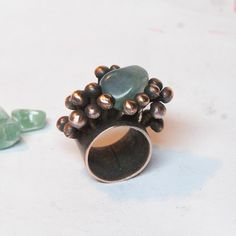This is a unique copper ring with small balls and stone. All of my jewerly is created in my home studio. Copper is a beautiful natural material