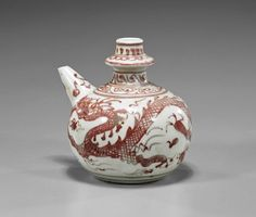 Yuan-Style Copper Red Kendi Yuan-style copper red underglaze porcelain kendi; of globular form with spout and flanged mouth, depicting a writhing dragon amid clouds, geometric border around mouth and neck (usual minor wear); H: 4 3/4""