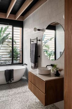 This House Addition Included A Vaulted Ceiling To Create More Open Space For The New Living Room, Dining Area, And Kitchen - In the bathroom, tiles cover the walls, while a freestanding bathtub is positioned beneath the wind -