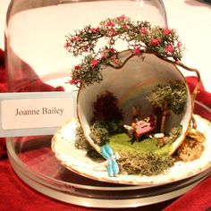 Joanne Bailey's Rural Picnic Scene in a Teacup - a cute way to display a mini scene (and I love the tree that wraps around the top, and bits of moss on the base - could be adapted to any fairy or mini scene