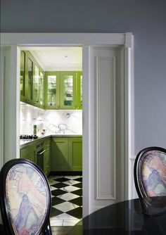 Contemporary kitchen with Granny Smith Apple green kitchen cabinets paired with calcutta marble countertops.