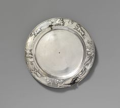 Silver plate. Imperial. 1st–2nd century A.D. Roman. Used over a prolonged period, since repeated polishing in antiquity has worn away the details of the rim decoration. On the underside are incised names of two different owners. It was common for Romans to mark their valuable possessions in this way as a precaution against theft. The use of masks, symbols, and animals as decoration seen here was popular throughout the Imperial period.