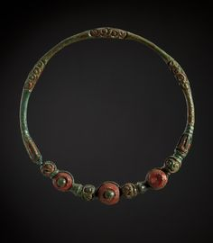 Scheibenhalsringe aus Gäufelden-Nebringen [Landesmuseum Württemberg] 2ndQ 4thC BC. Wheel collar ornamented with vine and scroll decorations. Celt. The green is patina on bronze, the red is glass.