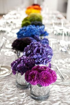 Stunningly simple rainbow flower centerpiece set against a white table.: Find your floral inspo at www.pinterest.com/laurenweds/wedding-flowers