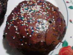 Chocolate muffin with chocolate icing and rainbow sprinkles