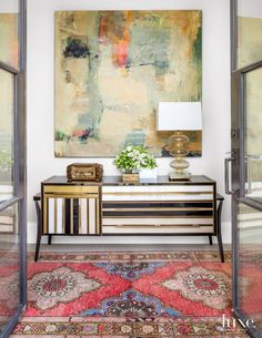 Seen through a custom steel door from Santiago Iron Works, an Italian Art Deco console that designer Cynthia Collins found during a Paris shopping trip sets the tone for the entry to a Dallas home; beneath it is an antique Oushak runner from Farzin Rugs. The Murano lamp is from Blue Print; artwork by Edie Maney is from The Arts Company in Nashville.