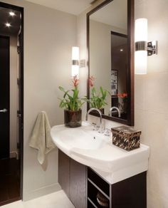 Sleek and lovely sconce lights next to the mirror in the bath