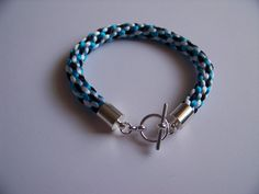 This Kumihimo Bracelet is made using 2mm Rattail in White, Turquoise, Pale Blue and Black.