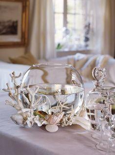 Bocal en verre avec des poissons décoré de coquillages pour jouer les centres de table