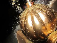 Buy yourself some gold spraypaint, gold glitter and big shiny ornaments. Right after spraying each ornament, dust the tops with glitter (before they dry.)  If they dry, just spray them again and sprinkle!