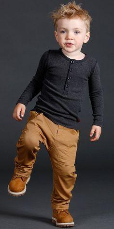 Niño mini fashionista vestido con un pantalón color café, camisa gris y botas timberland
