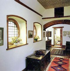 This is the upper landing from the Red House of William Morris in the UK.  William Morris is the father of the arts and crafts movement from the Victorian era.  The ceiling of this landing is covered in the famous arts and crafts style wallpaper.  The floor is decorated with a rug resembling native american print.  In the previous Empire era, rugs extend from wall to wall but not in the Victorian and especially the arts and crafts movement.