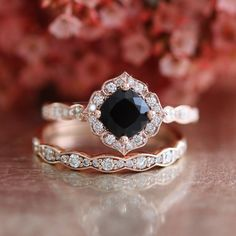 This mini vintage inspired bridal wedding ring set showcases a floral engagement ring with a 6x6mm cushion cut natural black spinel set in a solid