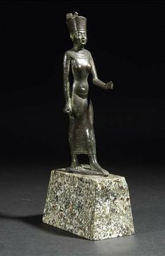 A bronze statuette of a walking queen, possibly the Godess NEITH, wearing the red crown of lower Egypt. - Property of an old German aristocratic collection. - Missing attributes, the crown uncomplete, the left arm broken and repaired.
