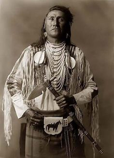 Pow Wow Photos – PowWows.com » » An Indian Standing and Holding his Tomahawk