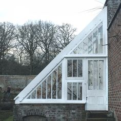 Greenhouse off shed with reclaimed / salvage windows. Good use of south side sun & early season plantings.