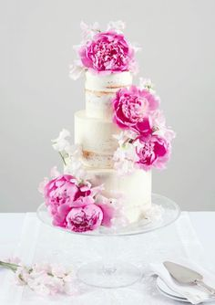 Featured Cake: Peggy Porschen Cakes; Pretty three tier white wedding cake topped with bright pink peonies