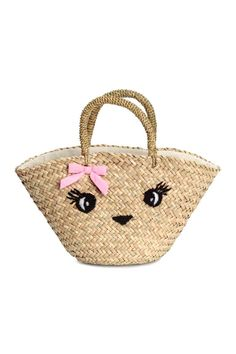 Seagrass beach bag: Small, sturdy bag in braided seagrass with embroidered details, a decorative cotton bow and short handles at the top. Lined. Size 12x18x34 cm.
