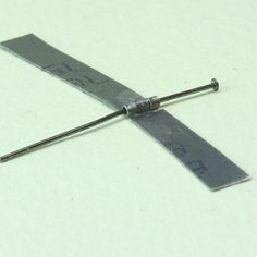 A jewelry head pin holds the sections of a simple dolls house scale hinge together.
