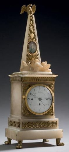 Alabaster & ormolu Obelisk Clock with an eagle with outstretched wings resting at the top of the obelisk. At the foot of the Obelisk lies a sheath of arms. The movement and the dial sit underneath the latter signed Tobias FLASCHGE in Vienna ; with small claw feet. Supporting the base - Austria, early nineteenth century. H: 51 L: 17 - P: 14 cm