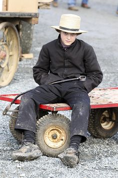 An older Amish boy, sits on a small wagon. Most children go to school through the 8th grade.....