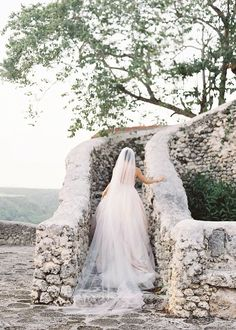 how picturesque is this bridal portrait captured by Carie King?The contrast of her long veil and the rough stone staircase is really lovely!
