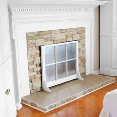 A salvaged window sash with added brackets enhances this fireplace when not in use.   thisoldhouse.com