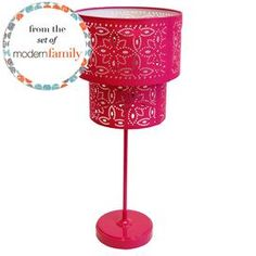 """Two-tiered pink table lamp with floral cutouts. From the set of ABC's Modern Family.  Product: Desk lampColor: PinkAccommodates: 1 Bulb - not includedDimensions: 19"""" H x  8.5"""" Diameter"""