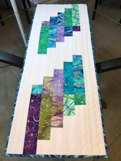 This is a beautiful handmade quilted table runner measuring 15 1/2 x 40 and is reversible. The top features blue, turquoise, green, lavender, purple and white. The fabric is 100% cotton and is from the Dance of the Dragonfly collection and you will find dragonflies in the fabric.