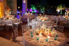"Wedding Reception at the Rosewood Mayakoba - The open-air reception allowed guests to enjoy Riviera Maya's warm ocean breeze all evening. Centerpieces overflowed with pink and purple roses, orchids, and greenery. ""We kept the centerpieces either very high or very low so everyone could see across the table,"" says Whitney. Candles in mercury holders lit the room as night fell."