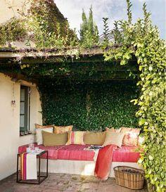 un banc en blanc et rose avec des coussins décoratifs sur la terrasse