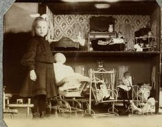Victorian photo of a girl standing by her large dollhouse.