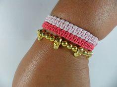 O kit é composto de:  * 1 pulseira caveira  * 2 pulseira macramê em tons de rosa...