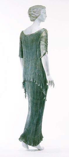 """Mariano Fortuny created a number of variations of his pleated silk gowns. In this model, he combined elements of the classical chiton and the peplos. A """"tunic"""" is attached along its neckline to a long sleeveless underdress, suggesting the apoptygma of the classical peplos. This effect is further emphasized by the handkerchief points at either hip, which would have been seen on the sides of an authentic apoptygma."""