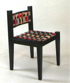 Chair by Marcel Breuer in collaboration with Gunta Stölzl<br /> Pear, polished black <br /> Seat and back of plaited woolen straps<br /> 1921<br /> <br /> 75.5x49x49 cm (HxWxD)<br /> <br /> Kunstsammlungen zu Weimar, Weimar