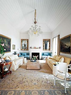 Plush seating coexists with lustrous gilt-edged mirrors and circular rosewood side tables in this Marabella, Spain living room.
