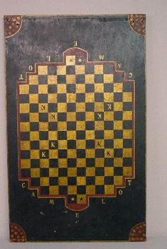 INTERESTING PAINT DECORATED GAMEBOARD. Poplar with old dry paint including gold and black blocks surrounded by red borders on a black ground. Red spandrels have gold stars in each corner.