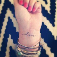 """Pequeño Tatuaje de la palabra """"love"""" en la muñeca, palabra en inglés que traducida al castellano significa """"amor""""."""