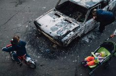"""May 3, 2014. Local citizens gather near destroyed vehicles that were burned by pro-Russian separatists in Kramatorsk, in eastern Ukraine. <br><br>From """"This is War."""" May 19, 2014 issue."""